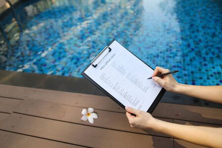 woman holds pen and application in UAE Dubai, contributes her data for new trip to foreign country. concept of signing papers, traveling to other countries. Front used with Open Font License