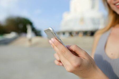 Close up beautiful girl speaking by smartphone near Buddha white statue in Phuket. Concept of tourism in Thailand and modern technology.