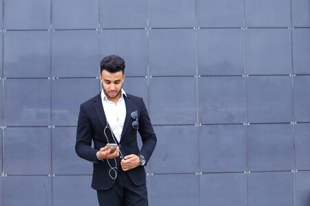 Entrepreneur takes makes selfie man male looking at camera and smiling talks on mobile smart phone. Young handsome businessman arab muslims in business center wearing dressed in black elegant suit on building background.