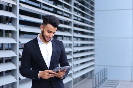 Young handsome businessman Arab Muslims is in the business center in black elegant dress on building background. Businessman man male looking waiting concept and smiling.