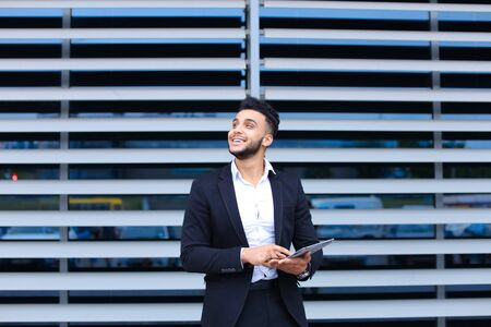 Entrepreneur uses tablet for online order shopping with debit credit card looking smiling at the camera. Young handsome businessman arab muslims in business center wearing dressed in black elegant suit on building background. Banco de Imagens