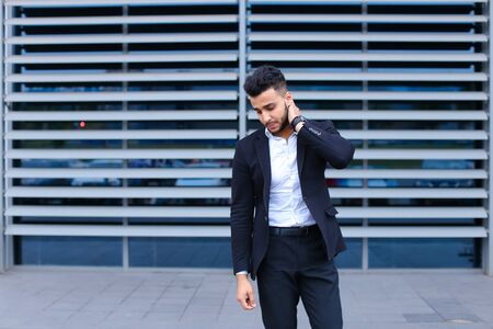 Entrepreneur shows neck pain tired looking at the camera. Young handsome businessman arab muslims in business center wearing dressed in black elegant suit on building background.