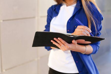 Girl holds in hands diary, black notebook with sheets and blue pen and writes in notebook. Young woman with light brown hair dressed in white T-shirt and bright blue shirt with pocket on arm bracelet.Concept of organization and planning of day, notebook, homework, busy dealer.