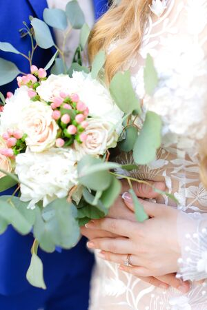 Close up bouquet of roses in bride and groom hands. Concept of flower composition and wedding photo session. Standard-Bild