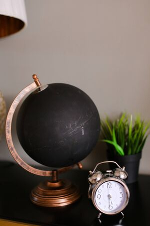 Black matte globe an alarm clock standing on wooden table near houseplant. Concept of geography cabinet and tourist agency.