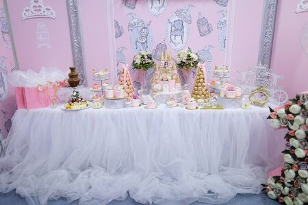 Many delicious sweet cakes and candies on decorated table. Concept of celebrating wedding and candy bar fow birthday.