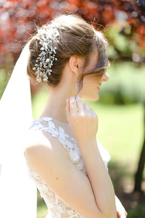 Back view portrait of caucasian bride wearing transparent veil and white dress. Concept of autumn wedding photo session in open air.