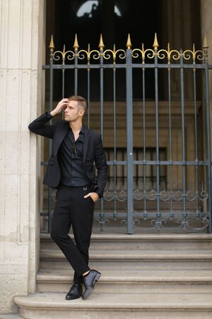 Young man standing on concrete stairs near metal gate and leaning on building. Concept of fashion male model. Boy wearing black suit. 写真素材