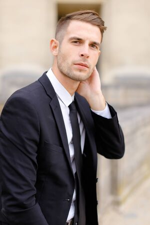 Portrait of young handsome man wearing black suit and leaning on concrete banister. Concept of of waiting groom and male wedding photo session.