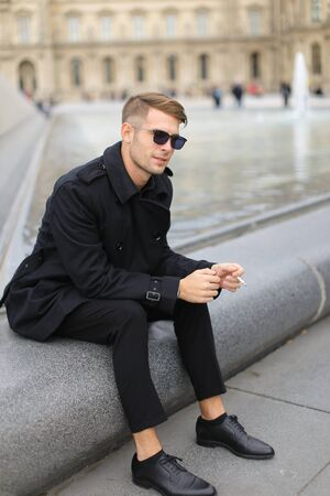Young smiling man in sunglasses wearing black clothes sitting near glass Louvre Pyramid in Paris and smoking cigarette, France. Concept of male fashion model and urban photo session.