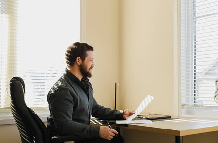 Thinking caucasian business boss sitting at office with documents, tablet on table. Concept of financial crisis because of coronavirus. Adult man working at cabinet. Standard-Bild