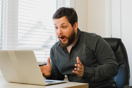 Successful broker sitting at office with laptop. Concept of modern technology and business success. Adult happy man using computer at cabinet.