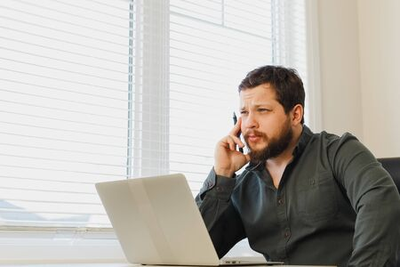 Caucasian male maanger sitting with pen and laptop at cabinet. Concept of office worker and modern technology. Adult man wearing shirt and surfing internet.