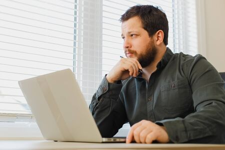 Thinking manager sitting, working online with laptop at cabinet and holding pen. Concept of financial crisis because of coronavirus. Adult man wearing shirt and surfing internet.