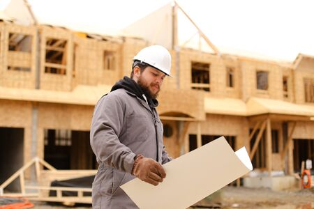 Foreman holding architecture drawing plan on paper at construction site and wearing hardhat. Concept of builder profession and house building. Standard-Bild