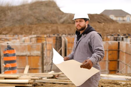 Male engineer holding drawing plan of hause at construction site, wearing white hardhat. Concept of hause building and builder profession. Standard-Bild