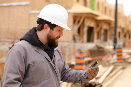 Caucasian builder using mobile phone internet at construction site and wearing hardhat. Concept of architectural profession and house building. Standard-Bild