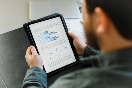 Closeup male economist using tablet and looking at graphs on screen. Concept of business project and executive person. Adult berarded man surfing internet by modern gadget. Reklamní fotografie