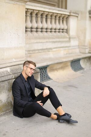 Young handsome man sitting on sidewalk ground and wearing black suit, leaning on concrete banister. Concept of walking in cty and male fashionable model.