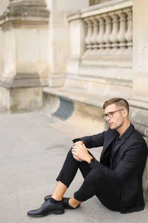 Young stylish man sitting on sidewalk ground and wearing black suit, leaning on concrete banister. Concept of walking in cty and male fashionable model.