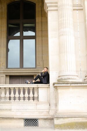 Young caucasian european boy sitting on balcony concrete banister in Paris. Concept of architecture and male fashion model. Guy wearing black suit and walking in city. Standard-Bild