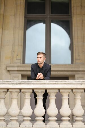 Young european boy leaning on balcony concrete railing in Paris. Concept of male fashon moden and architecture. Guy wearing black suit.