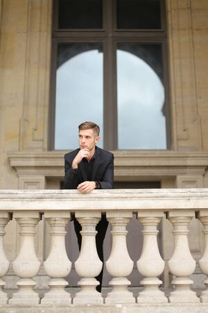 Young european handsome boy leaning on balcony concrete railing in Paris. Concept of male fashon moden and architecture. Guy wearing black suit.