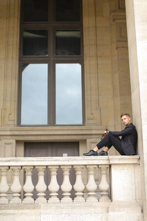 Young caucasian handsome boy sitting on balcony concrete banister in Paris. Concept of architecture and male fashion model. Guy wearing black suit and walking in city.