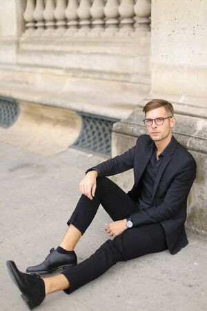Young european man sitting on sidewalk ground and wearing black suit, leaning on concrete banister. Concept of walking in cty and male fashionable model.