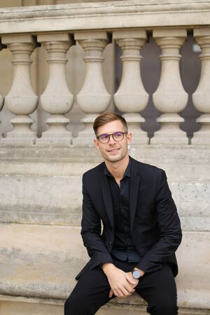 Young handsome man sitting on sidewalk and leaning on concrete railing of building, wearing black suit and glasses. Concept of walkig in city, urban photo session and male person model. Standard-Bild
