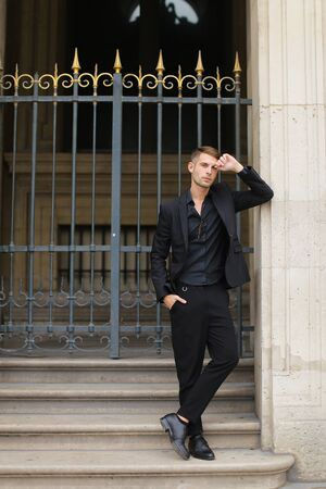 Young handsome man standing near metal gate and leaning on building. Concept of fashion male model. Boy wearing black suit.