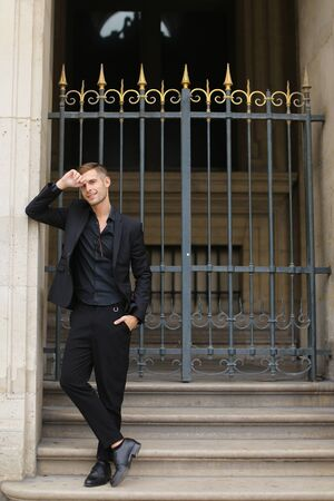 Young european man standing near metal gate and leaning on building. Concept of fashion male model. Boy wearing black suit.