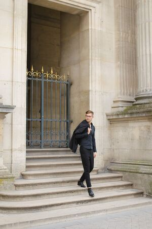 Young man walking on concrete stairs, metal gate in background. Concept of male fashion and model. Boy wearing black suit.