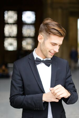 Young groom wearing black suit and waiting, loking at watch. Concept of male model and businessman. Standard-Bild