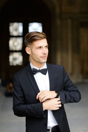 Young man standing and posing, wearing black suit and bow tie, window in background. Concept of fashionable businessman and male model.