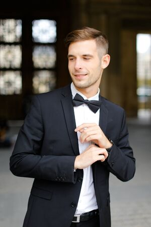 Young handsome man standing and posing, wearing black suit and bow tie, window in background. Concept of fashionable businessman and male model. Standard-Bild