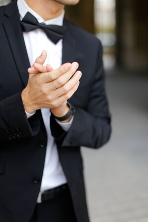 Close up man clapping and wearing black suit with bow tie. Concept of business trip and executive person on conference.