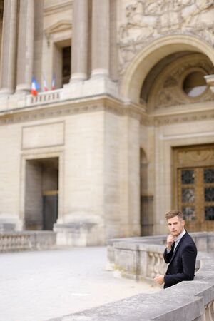 Young european groom waiting and leaning on concrete banister near building. Concept of wedding male photo session or businessperson. Man wearing black suit. Standard-Bild