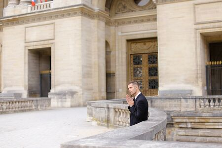 Young caucasian groom waiting and leaning on concrete banister near building. Concept of wedding male photo session or businessperson. Man wearing black suit. Standard-Bild