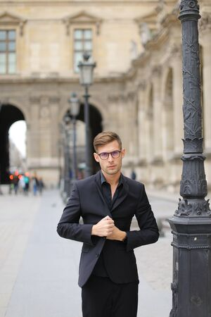 Young handsome man walking in Paris and leaning on lantern, weaaring black suit. Concept of walking in city and male fashion.