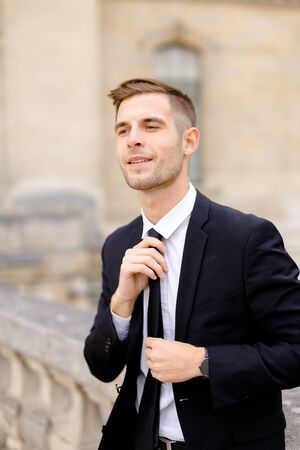 Portrait of young groom straightening tie and wearing black suit, leaning on concrete banister. Cncept of business or groom photo session. Standard-Bild