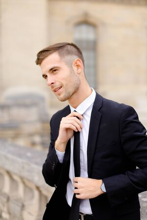 Portrait of young caucasian groom straightening tie and wearing black suit, leaning on concrete banister. Cncept of business or groom photo session.