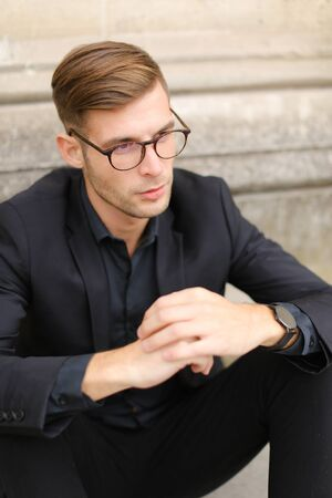 Portrait of man wearing black suit and glasses, sitting on sidewalk ground. Concept of male beauty and fashionable model.
