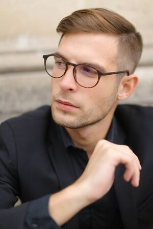 Closeup portrait of man wearing black suit and glasses, sitting on sidewalk ground. Concept of male beauty and fashionable model.