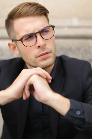 Closeup portrait of handsome man wearing black suit and glasses, sitting on sidewalk ground. Concept of male beauty and fashionable model. Standard-Bild