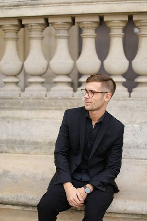 Young caucasian man sitting on sidewalk and leaning on concrete railing of building, wearing black suit and glasses. Concept of walkig in city, urban photo session and male person model. Standard-Bild