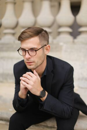 Young fashionable man sitting on sidewalk and leaning on concrete railing of building, wearing black suit and glasses. Concept of walkig in city, urban photo session and male person model.