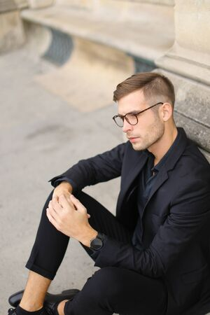 Young fashionable man sitting on sidewalk ground and wearing black suit, leaning on concrete banister. Concept of walking in cty and male stylish model.