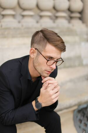 Young european man sitting on sidewalk and leaning on concrete railing of building, wearing black suit and glasses. Concept of walkig in city, urban photo session and male person model. Standard-Bild