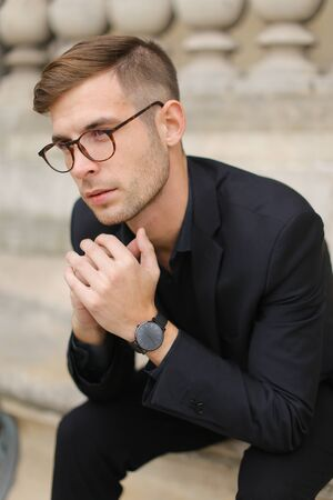 Young handsome male person sitting on sidewalk and leaning on concrete railing of building, wearing black suit and glasses. Concept of walkig in city, urban photo session and male person model.